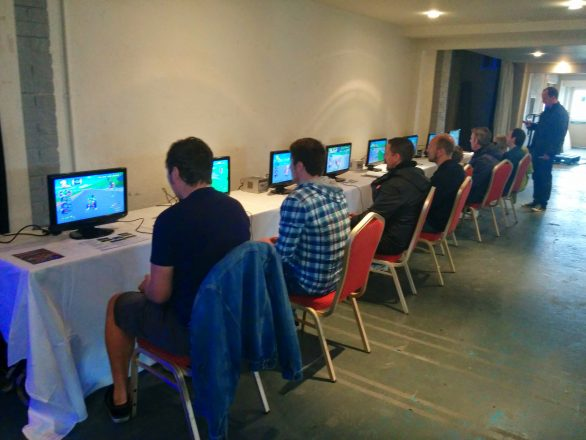 8 People sat in front of 8 Nintendo GameCubes playing Mario Kart Double Dash